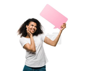Photo for Cheerful african american girl looking at pink speech bubble isolated on white - Royalty Free Image