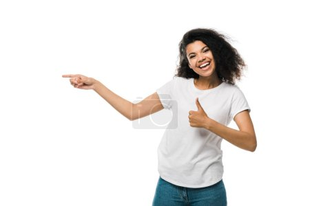 cheerful african american girl showing thumb up and pointing with finger isolated on white