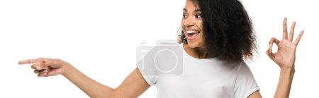 Photo pour Plan panoramique de femme afro-américaine joyeuse pointant du doigt tout en montrant ok signe isolé sur blanc - image libre de droit
