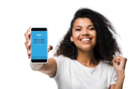Photo pour KYIV, UKRAINE - 29 MAI 2019 : mise au point sélective de fille afro-américaine heureuse tenant smartphone avec application skype et célébrant isolé sur blanc - image libre de droit