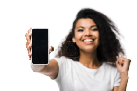 Photo for Selective focus of positive african american girl holding smartphone with blank screen and celebrating isolated on white - Royalty Free Image