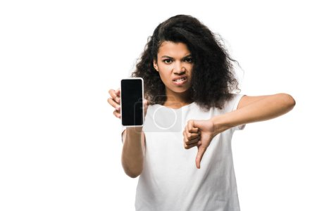 Photo pour Mécontent afro-américaine fille tenant smartphone avec écran blanc et montrant pouce vers le bas isolé sur blanc - image libre de droit