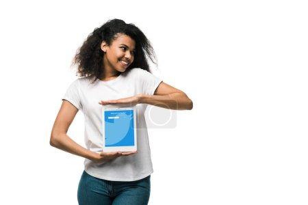 Photo for KYIV, UKRAINE - MAY 29, 2019: happy african american girl holding digital tablet with twitter app on screen isolated on white - Royalty Free Image