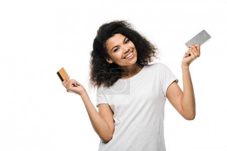 fröhliche afrikanisch-amerikanische Frau hält Kreditkarte und Smartphone isoliert auf weiß