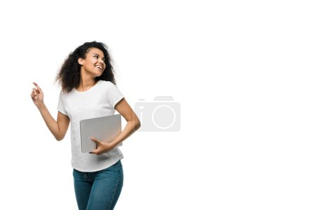 Photo for Cheerful young african american woman gesturing while holding laptop isolated on white - Royalty Free Image