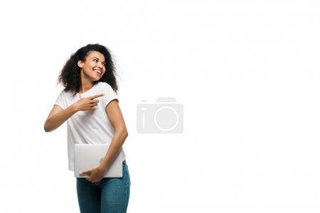Photo pour Jeune femme américaine africaine heureuse pointant avec le doigt tout en retenant l'ordinateur portatif d'isolement sur le blanc - image libre de droit