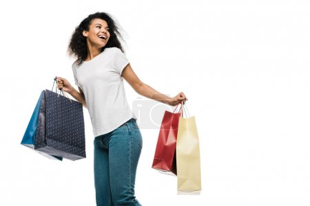 Photo for Cheerful curly african american girl holding shopping bags isolated on white - Royalty Free Image