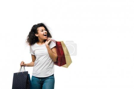 joyeuse jeune femme afro-américaine bouclée tenant des sacs à provisions isolés sur blanc