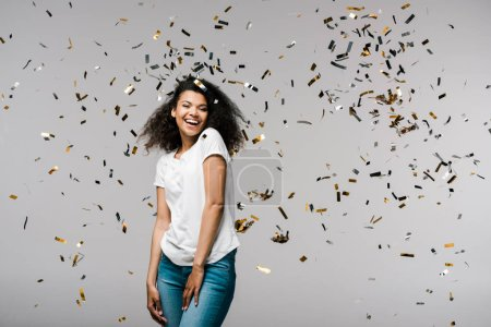 Photo for Happy young african american woman smiling near shiny confetti while standing on grey - Royalty Free Image