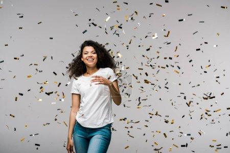 Photo pour Jeune femme afro-américaine souriant près de confettis brillants tout en se tenant sur gris - image libre de droit