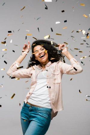 Photo pour Positive jeune femme afro-américaine souriant près de confettis brillants tout en se tenant sur gris - image libre de droit