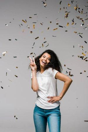 Photo pour Jeune femme américaine africaine souriant près des confettis brillants tout en restant avec la main sur la hanche et affichant le signe de paix sur le gris - image libre de droit