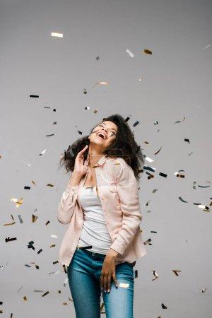 Foto de Mujer afroamericana feliz sonriendo cerca de caer confeti mientras está de pie en gris - Imagen libre de derechos