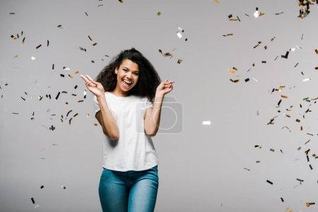 Photo pour Jeune femme américaine africaine souriant près de tomber des confettis tout en restant et affichant le signe de paix sur le gris - image libre de droit