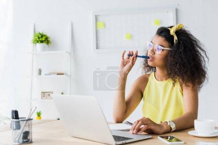 Cher jeune femme afro-américaine dans des lunettes tenant stylo tout en étant assis près d'un ordinateur portable
