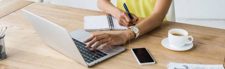 Photo for Panoramic shot of african american woman holding pen near notebook and laptop - Royalty Free Image