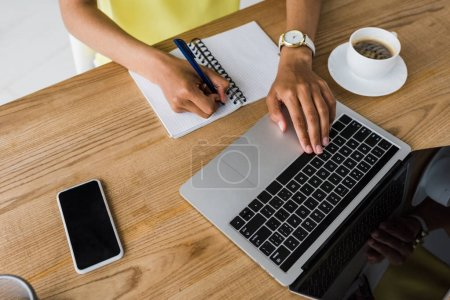 Photo for Overhead view of african american woman holding pen near notebook and laptop with blank screen - Royalty Free Image