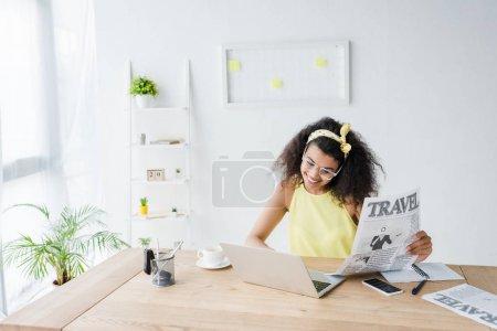 Photo pour Femme américaine africaine gaie regardant l'ordinateur portatif et retenant le journal de voyage - image libre de droit
