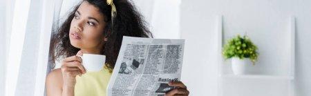 Photo pour Plan panoramique de brune frisée afro-américaine tenant journal et tasse avec boisson - image libre de droit