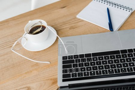 Photo for Selective focus of saucer and cup of coffee near laptop and notebook - Royalty Free Image