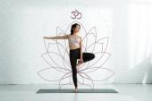 "Постер, картина, фотообои ""attractive asian woman doing yoga exercise near lotus flower on white """