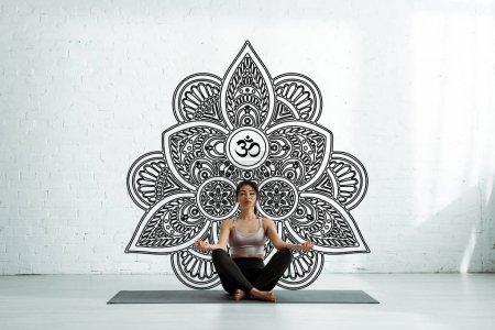 Photo pour Calm asian woman with closed eyes sitting on yoga mat near mandala ornament - image libre de droit