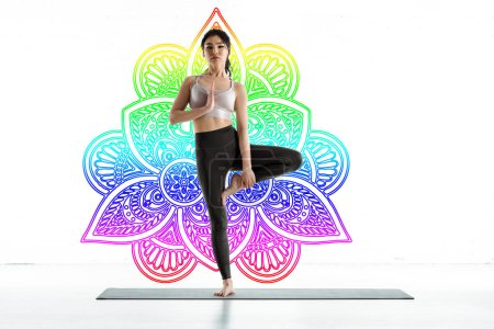 Photo pour Thai woman practicing yoga on yoga mat near colorful mandala ornament on white - image libre de droit