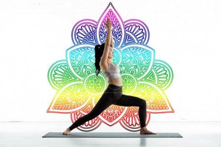 Photo pour Femme asiatique pratiquant le yoga sur le tapis de yoga près de l'ornement coloré de mandala sur le blanc - image libre de droit