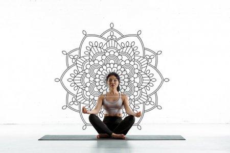 Photo pour Femme thaïcalme calme pratiquant le yoga sur le tapis de yoga près de l'ornement de mandala sur le blanc - image libre de droit