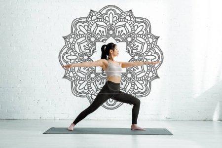 Photo pour Calm asian woman standing with outstretched hands on yoga mat near mandala ornament - image libre de droit