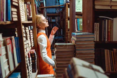 Photo for Pretty and blonde woman in orange dress and glasses standing in library - Royalty Free Image