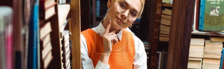 Photo for Panoramic shot of pretty and blonde woman in glasses looking away in library - Royalty Free Image