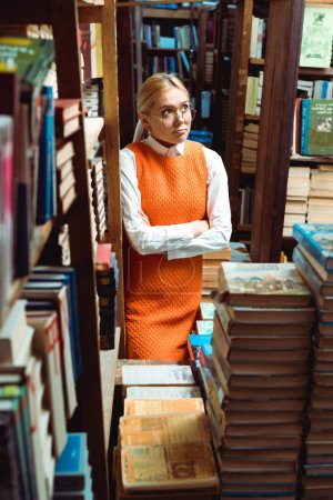 Photo for Pretty and sad woman in glasses and orange dress with crossed arms looking away in library - Royalty Free Image