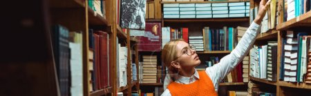 Photo for Panoramic shot of pretty and blonde woman in glasses holding book in library - Royalty Free Image