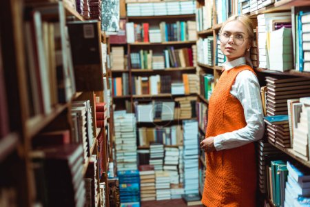 Photo for Beautiful and blonde woman in glasses and orange dress standing and looking away in library - Royalty Free Image