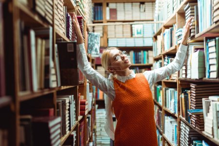 Foto de Mujer bonita y rubia en gafas y vestido naranja mirando hacia otro lado en la biblioteca - Imagen libre de derechos