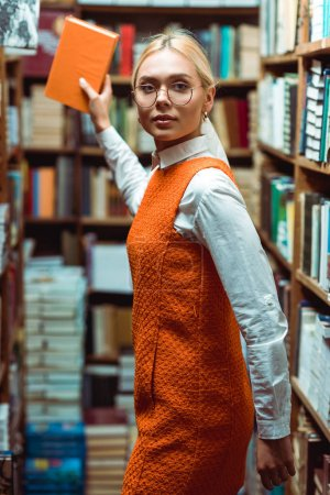 Photo for Blonde and beautiful woman in glasses and dress holding book and looking at camera in library - Royalty Free Image