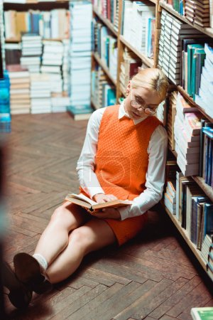 Photo for Blonde and beautiful woman in glasses and orange dress sitting on floor and reading book in library - Royalty Free Image