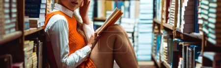 Photo for Panoramic shot of woman in orange dress holding book in library - Royalty Free Image