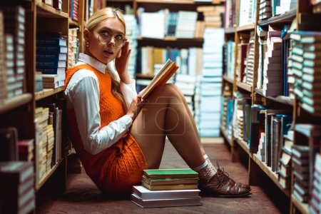 Photo for Beautiful and blonde woman in glasses holding book and sitting on floor in library - Royalty Free Image
