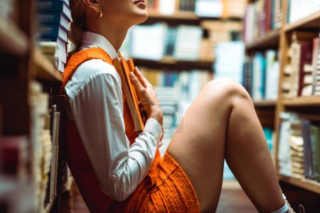 Photo for Cropped view of woman in orange dress holding book in library - Royalty Free Image
