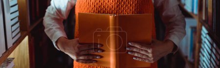 Photo for Cropped view of woman holding orange book with copy space in library - Royalty Free Image
