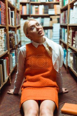 Foto de Beautiful and dreamy woman in glasses sitting on floor and looking away in library - Imagen libre de derechos