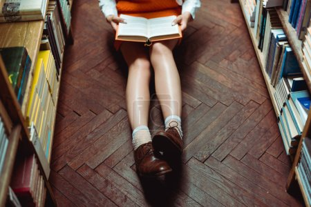 Photo for Partial view of woman sitting on wooden floor and holding book - Royalty Free Image
