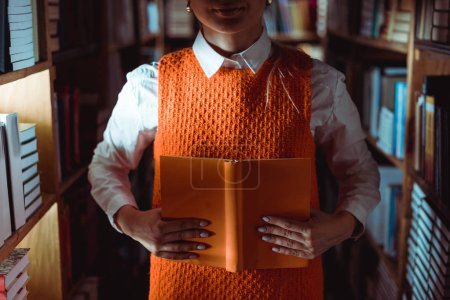 Photo for Partial view of woman in dress holding orange book with copy space in library - Royalty Free Image