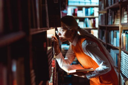 Photo for Pretty woman in glasses looking away and holding book in library - Royalty Free Image