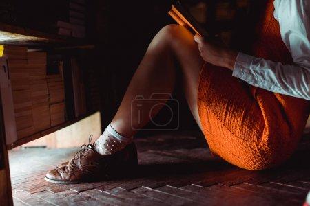 Photo pour Vue recadrée de la femme assise sur le sol en bois et tenant le livre dans la bibliothèque - image libre de droit