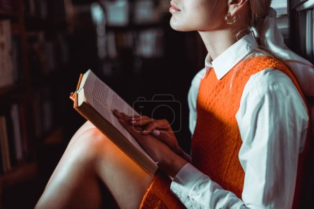 Photo for Cropped view of woman in orange dress sitting and holding book in library - Royalty Free Image