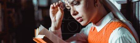 Photo pour Plan panoramique de belle femme tenant des lunettes et un livre de lecture dans la bibliothèque - image libre de droit