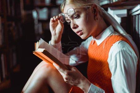 Photo pour Belle femme blonde retenant des glaces et lisant le livre dans la bibliothèque - image libre de droit